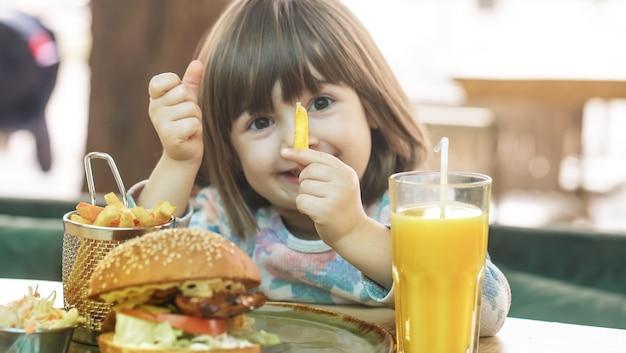 Piccola ragazza carina che mangia un panino fast food con patatine fritte e succo d'arancia in un caffè. concetto di fast food.