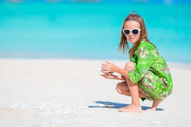 Piccola ragazza carina con conchiglia in mano in spiaggia tropicale. bambina adorabile che gioca con i seashells sulla spiaggia