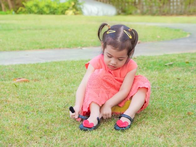 Piccola ragazza carina di 3 anni con vestito arancione cercando di mettere le scarpe.