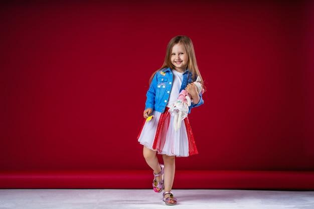 Piccola ragazza carina in abiti alla moda che abbraccia il suo animale giocattolo preferito