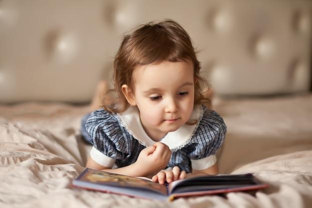 Piccola ragazza carina in un abito retrò, leggendo un libro.