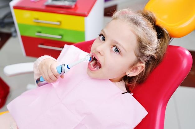 Piccola ragazza carina senza denti di latte anteriori in poltrona dentale rossa con spazzolino elettrico automatico nelle mani.