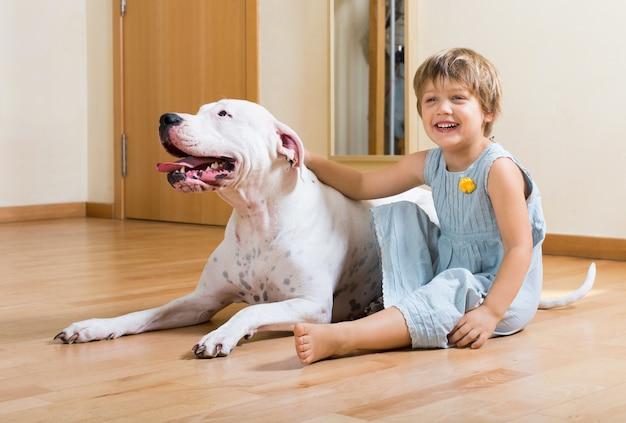 Piccola ragazza carina sul pavimento con il cane