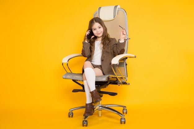 Piccola ragazza castana in sedia