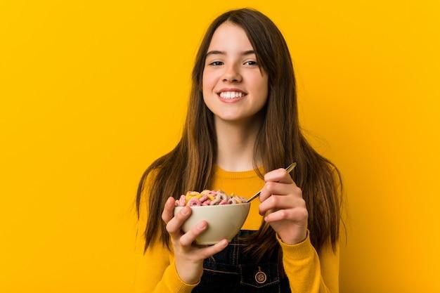 Piccola ragazza caucasica che tiene una ciotola di cereali