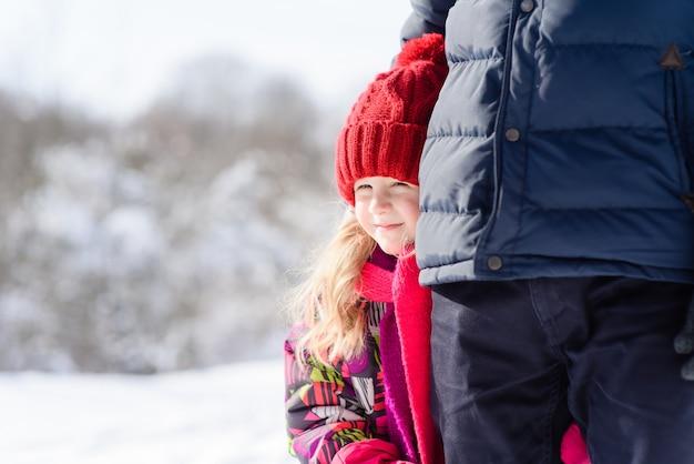 Piccola ragazza che resta vicino al padre in inverno