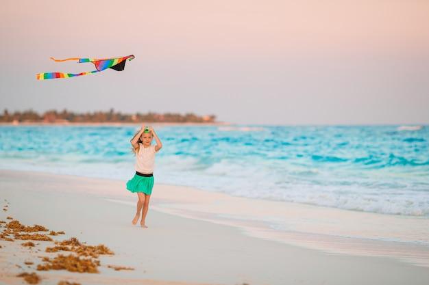 Piccola ragazza corrente con l'aquilone di volo sulla spiaggia tropicale. gioco per bambini sulla riva dell'oceano.