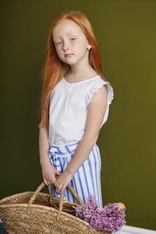 Piccola ragazza dai capelli rossi con un cesto di fiori