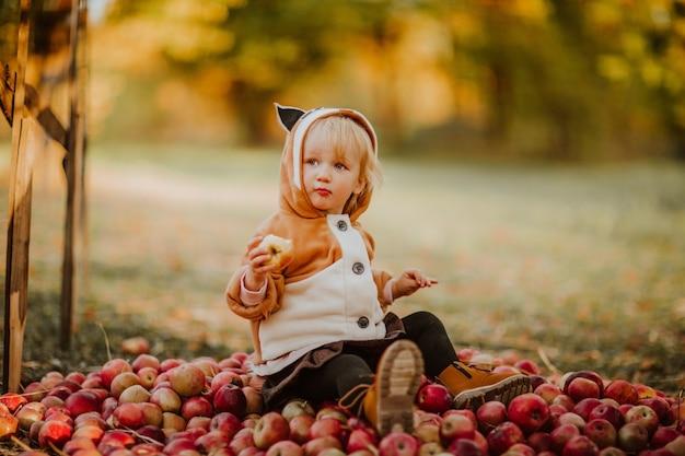 Piccola ragazza del bambino in cappotto di volpe che mangia mela che si siede sulla collina di una mela. copia spazio