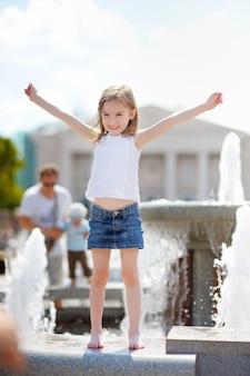 Piccola ragazza del bambino in età prescolare che gioca con una fontana della città il giorno di estate