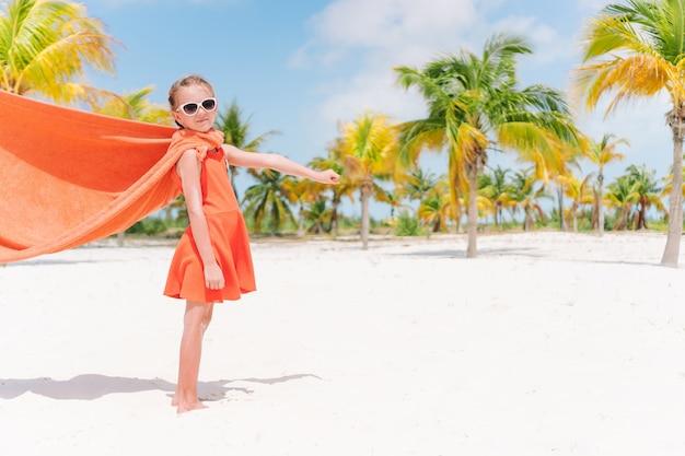 Piccola ragazza del cutie che gioca supereroe ad una spiaggia tropicale