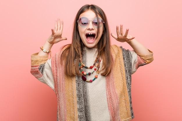 Piccola ragazza del hippie che celebra una vittoria o un successo