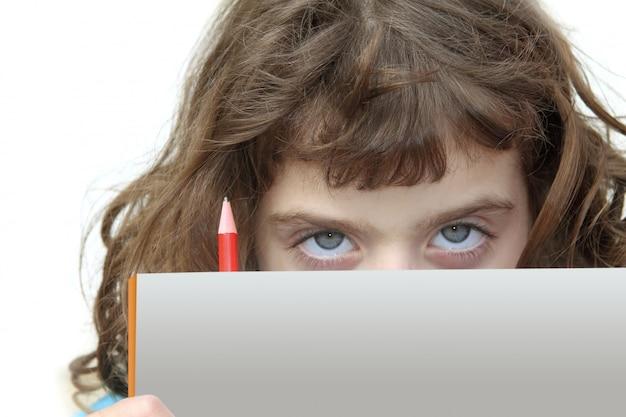 Piccola ragazza dell'allievo che osserva dietro il libro con la matita