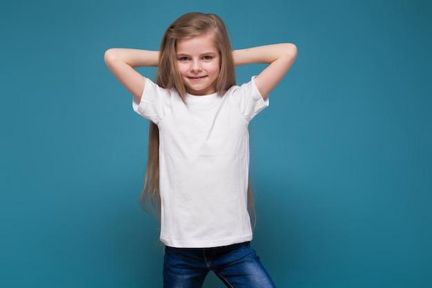 Piccola ragazza di bellezza in maglietta con lunghi capelli castani