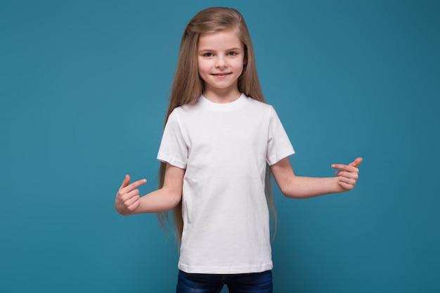 Piccola ragazza di bellezza in t-shirt con lunghi capelli castani