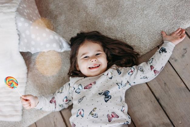Piccola ragazza divertente del brunette in pigiami accoglienti con la lecca-lecca sul pavimento