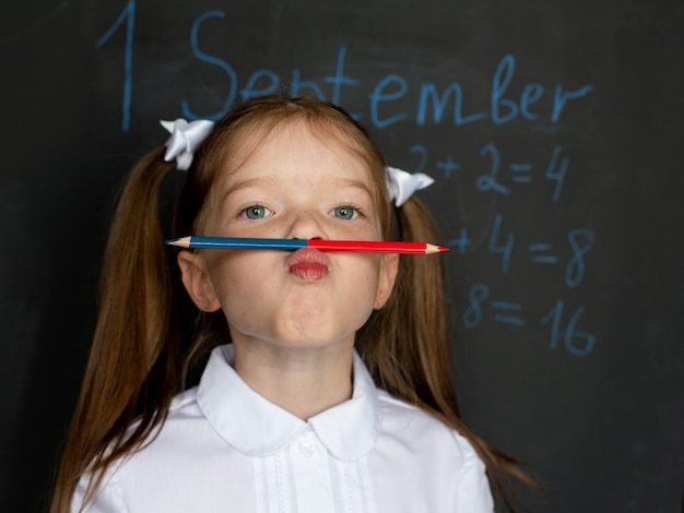 Piccola ragazza divertente in uniforme scolastica sta alla lavagna, tiene una matita sotto il naso.
