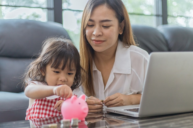 Piccola ragazza e madre asiatiche adorabili che mettono soldi nel porcellino salvadanaio per risparmiare