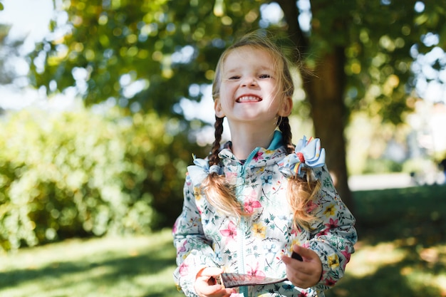 Piccola ragazza felice bianca con due trecce in una giacca multicolore guardando la telecamera e sorridente in una calda giornata d'autunno