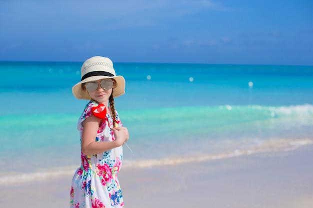Piccola ragazza felice con cuore rosso in mani su una spiaggia tropicale