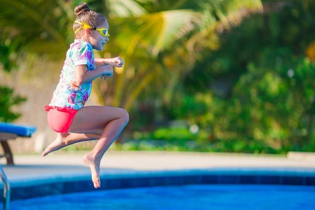 Piccola ragazza felice divertendosi nella piscina all'aperto