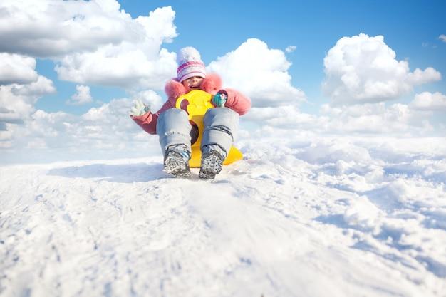 Piccola ragazza felice in abbigliamento invernale che guida in discesa