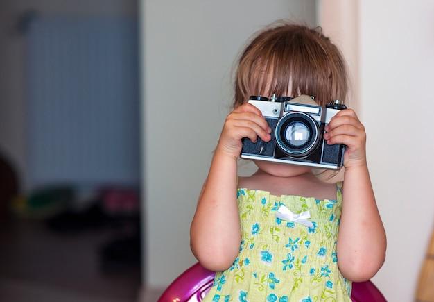 Piccola ragazza felice sveglia con la macchina fotografica d'annata della foto
