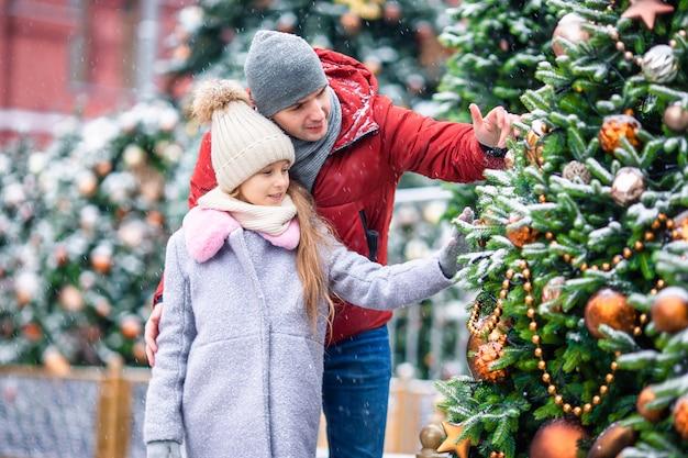Piccola ragazza felice vicino al ramo dell'abete in neve per il nuovo anno.