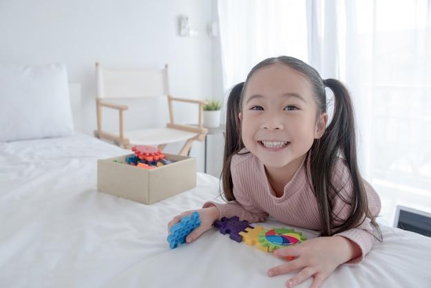 Piccola ragazza indiana / asiatica sveglia che gode mentre giocando con i giocattoli o i blocchi