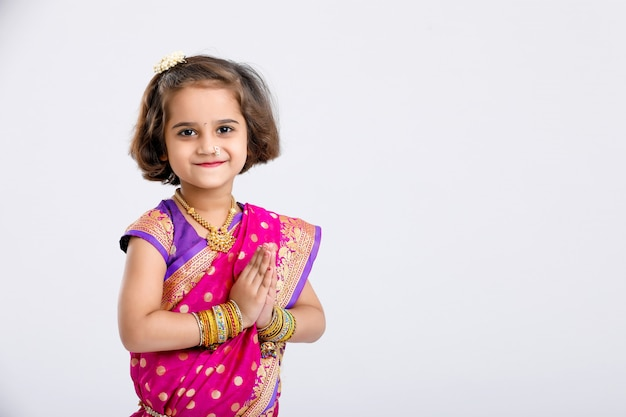 Piccola ragazza indiana / asiatica sveglia nella posa pregante