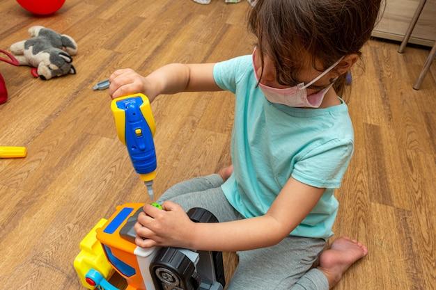 Piccola ragazza nella maschera medica che gioca con il trattore del costruttore del giocattolo a casa