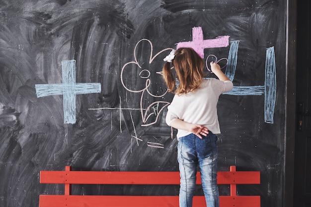 Piccola ragazza riccia che disegna con il colore del pastello sulla parete. opere di bambino. scrittura sveglia dell'allievo sulla lavagna