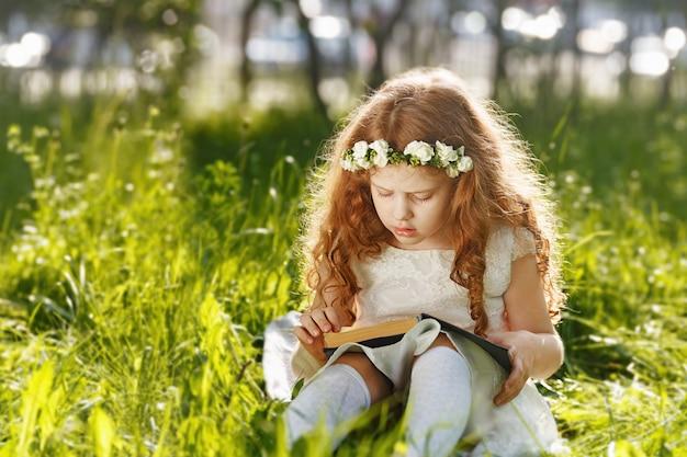 Piccola ragazza riccia pregando, sognando o leggendo un libro in mezzo alla natura.