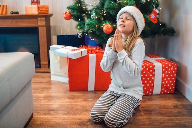 Piccola ragazza seduta in ginocchio e pregando.