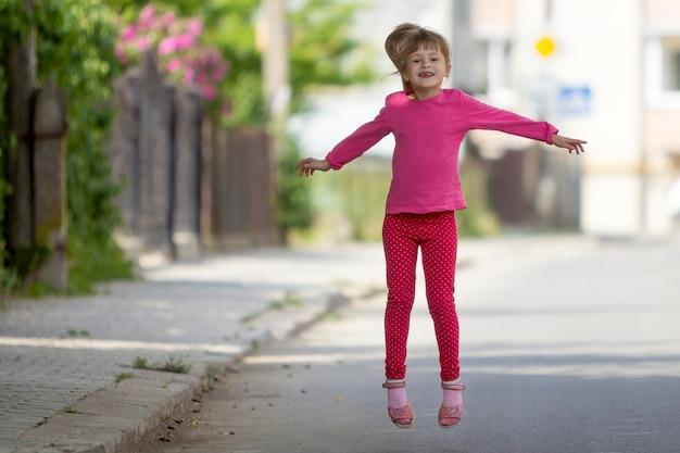 Piccola ragazza senza denti sorridente divertente sveglia in abbigliamento casual rosa con il salto biondo lungo della coda di cavallino