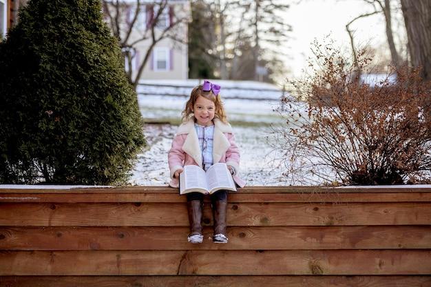 Piccola ragazza sorridente allegra che si siede sulla veranda in legno e che tiene un libro