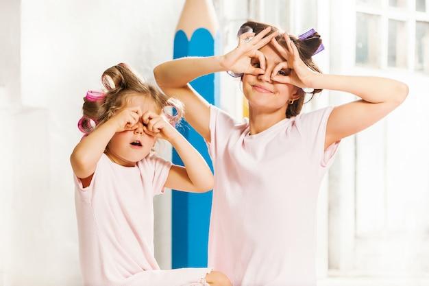 Piccola ragazza sorridente che gioca con sua madre su bianco