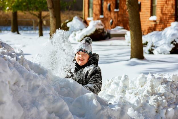 Piccola ragazza sorridente felice all'aperto nella neve in vestiti di inverno