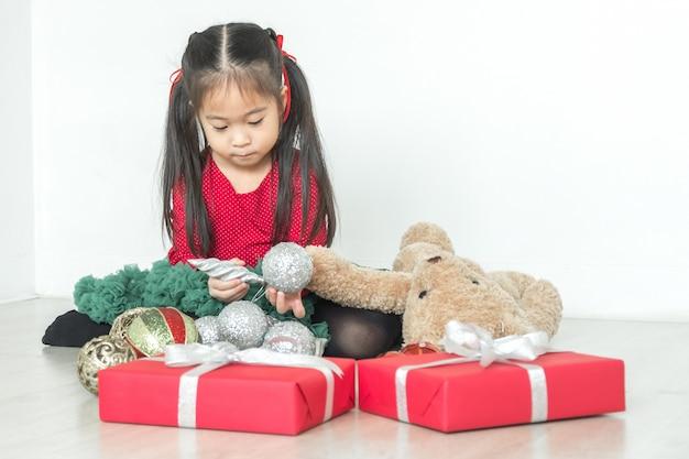 Piccola ragazza sorridente felice con il contenitore di regalo di natale.