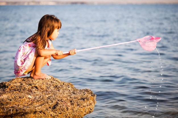 Piccola ragazza sorridente in swimvear luminoso che sta nel sole e che esamina poca pietra con il fondo del cielo blu