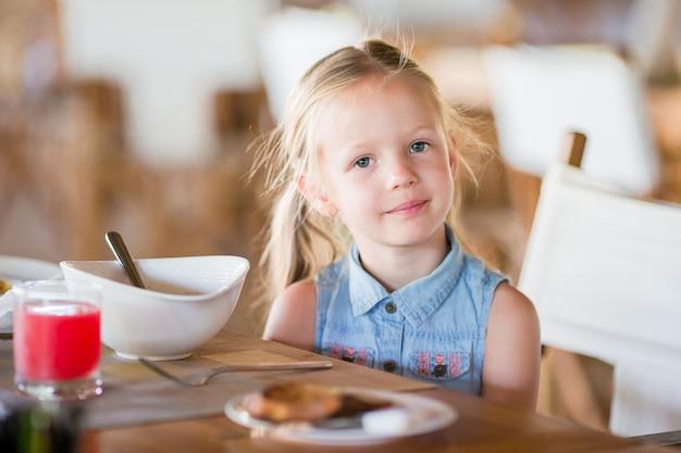 Piccola ragazza sorridente pranzando in caffè all'aperto