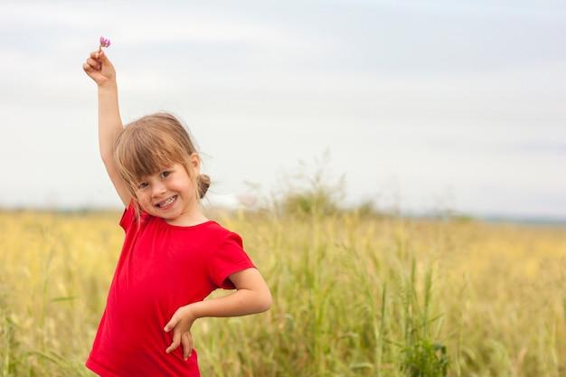 Piccola ragazza sorridente sveglia che giudica piccolo fiore disponibile