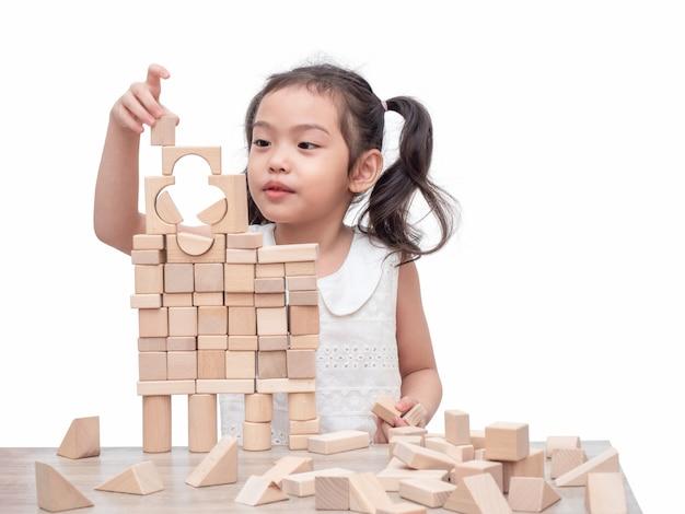 Piccola ragazza sveglia 6 anni che gioca i blocchi di legno sulla tavola e sul fondo bianco.