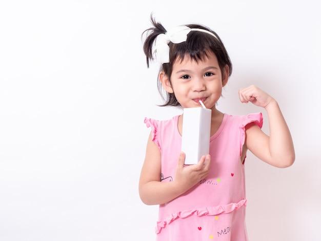 Piccola ragazza sveglia asiatica 3 anni che tengono e che bevono latte dal cartone di latte sopra fondo bianco.