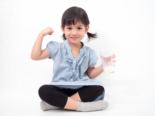 Piccola ragazza sveglia asiatica 4 anni che tiene e che beve latte dai vetri e che alza il suo braccio per essere forte sulla parete bianca