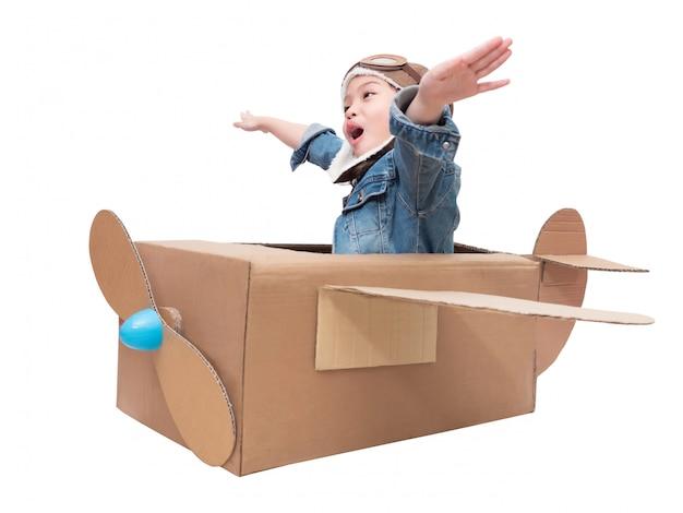 Piccola ragazza sveglia asiatica 6 anni che gioca l'aeroplano di cartone isolato su bianco con il percorso di ritaglio. bambino gioca come pilota su aeroplano di cartone fai-da-te.