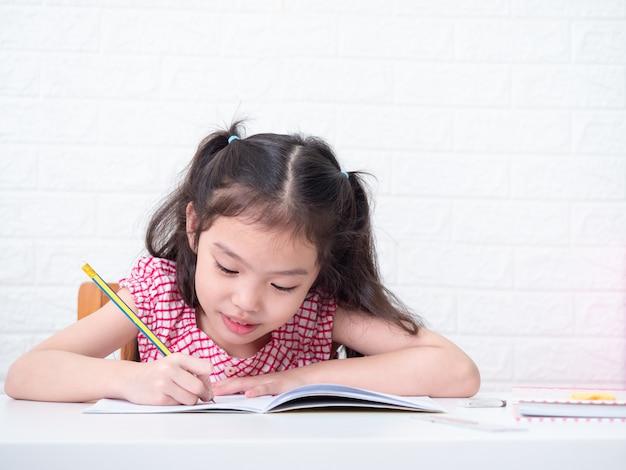 Piccola ragazza sveglia asiatica 6 anni che si siedono e che scrivono alla nota sulla tavola bianca. compiti adorabili prescolari di scrittura del bambino a casa.