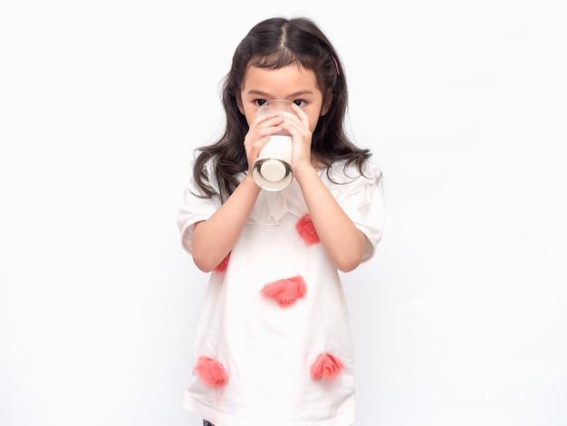 Piccola ragazza sveglia asiatica 6 anni che tiene e che beve latte dai vetri