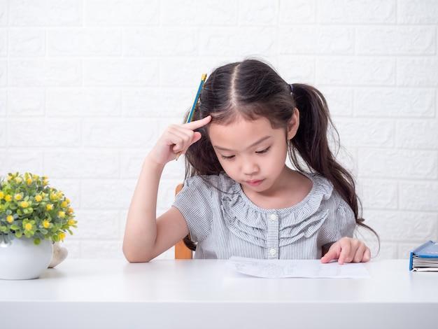 Piccola ragazza sveglia asiatica di 6 anni che pensa seriamente ai compiti di matematica sopra il muro di mattoni bianco e la tavola bianca. apprendimento ed educazione
