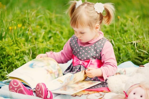 Piccola ragazza sveglia che legge un libro nel giorno soleggiato caldo in primavera